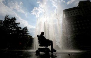 Miguel Torres, 77, rides his electric wheelchair near a fountain at Pier A Park while escaping his hot apartment, Wednesday, July 17, 2013, in Hoboken, N.J. (AP Photo/Julio Cortez)